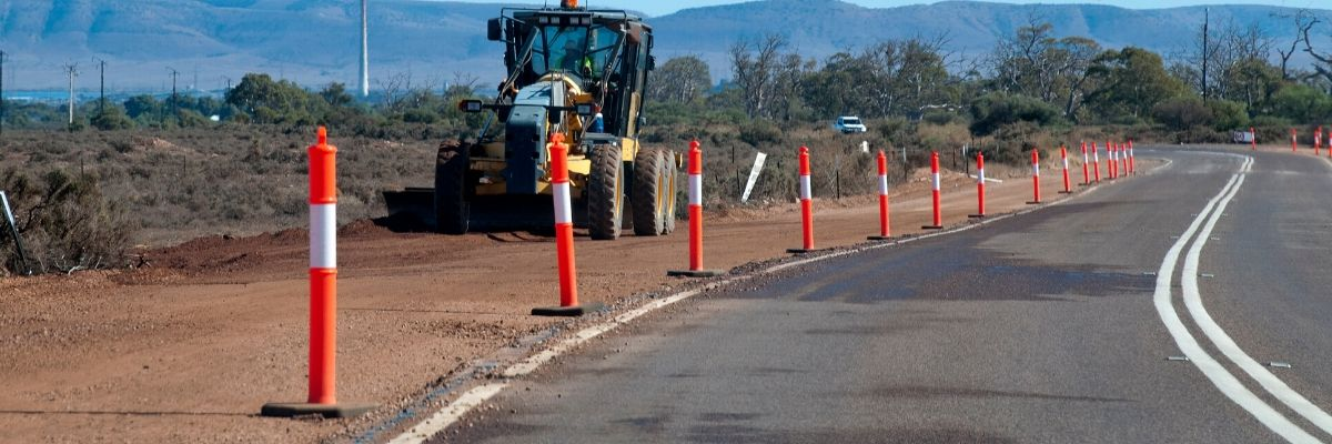 Roadworks set up with orange cones along a highway