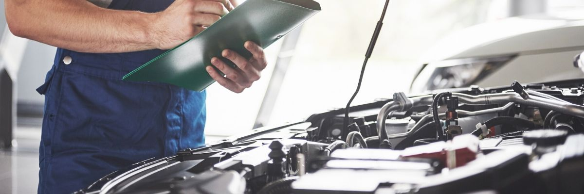 DO I need a pre-purchase vehicle inspection? Mechanic looking over car.